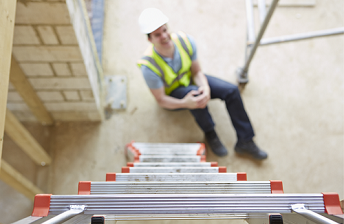 Man wearing safety vest and hard hat sits at the bottom of a ladder holding his right knee